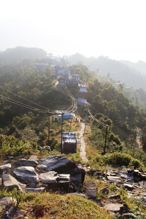 في جزء عالٍ من القرية فوق بعض الأدراج الصخرية ويبدو جزء من الدرب الذي يتسع فقط للمشاة.